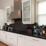 Wire-Brushed Natural Hickory Wood Flooring in Kitchen with black glass back splash