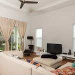 Wire-Brushed Natural Hickory Wood Flooring in Living Room with Curtains and tall ceilings