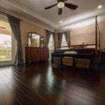 Spanish Hickory Blackhills Wood Flooring in Bedroom with tan walls